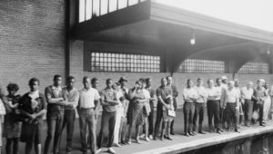 People wait on a train platform to pay respects as the Robert Kennedy Funeral Train passes by.