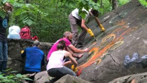 Volunteers from the Haycock Bouldering Coalition clean graffiti from rocks at Nockamixon State Park