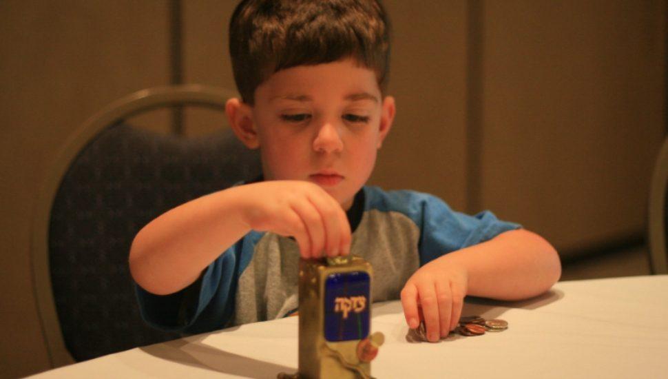 little boy filling tzedakah box