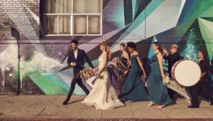 Wedding party walking down the sidewalk.